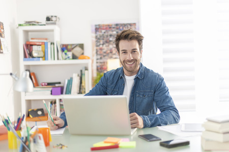 young man working on a laptop indoors Stock Photo