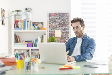 desk work: young man working on a laptop indoors Stock Photo