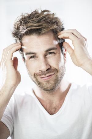 coiffer: closeup portrait d'un homme beau examiner ses cheveux Banque d'images