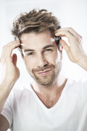 man hair: closeup portrait of an handsome man examining his hairs Stock Photo