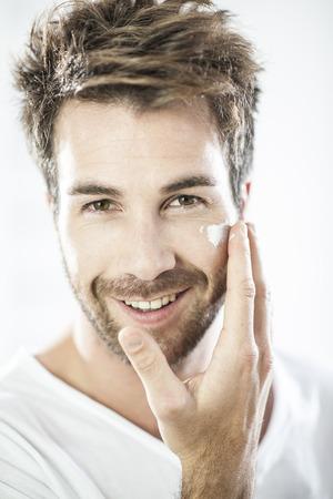 rostro hombre: primer plano sobre el hombre de aplicar la crema en la cara Foto de archivo