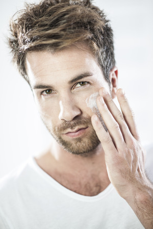 man face close up: closeup on man applying cream on his face