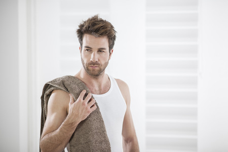 handsome man in his bathroom towel on shoulders Stock Photo