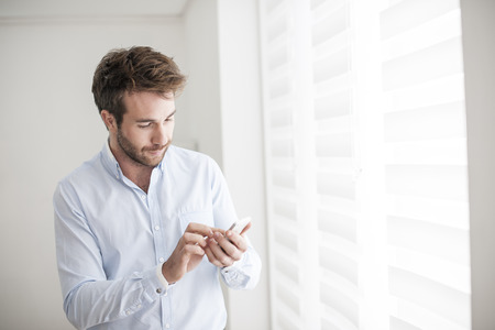young man at phone typing an sms Standard-Bild