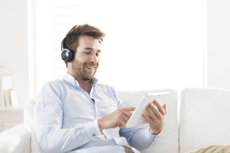 man  listening music with headphone and digital tablet Stock Photo