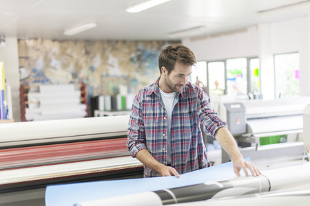 printing industry: worker in a workshop with machines at the background