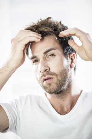 closeup portrait of an handsome man examining his hairs Standard-Bild