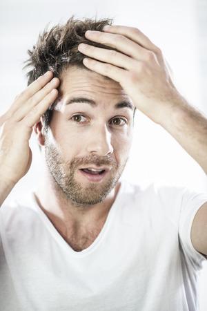 hair loss: closeup portrait of an handsome man examining his hairs Stock Photo