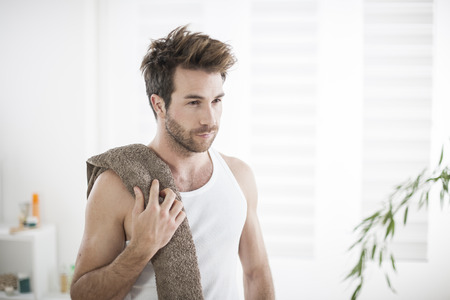 man face close up: handsome man in his bathroom towel on shoulders Stock Photo