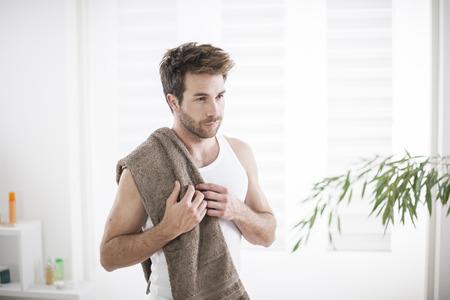 handsome man in his bathroom towel on shoulders Stock Photo