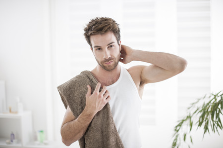 handsome man in his bathroom towel on shoulders photo