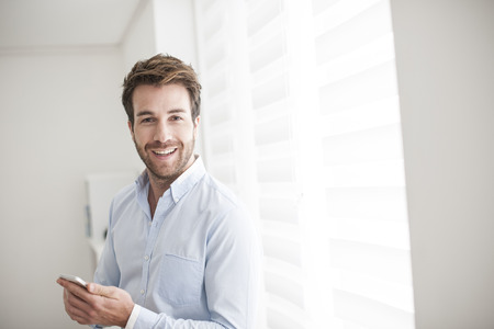 only one mid adult male: young man at phone receives a good news