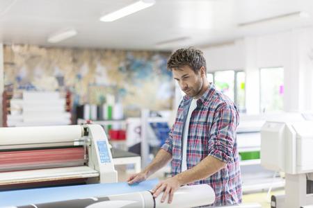 estampado: trabajador en un taller con m�quinas en el fondo