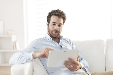 handsome man surfing an tablet