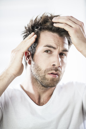 expressive mood: closeup portrait of an handsome man examining his hairs Stock Photo
