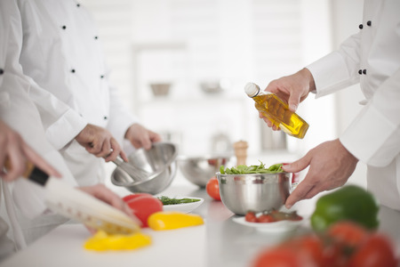 anonymous hands preparing food in professional kitchen