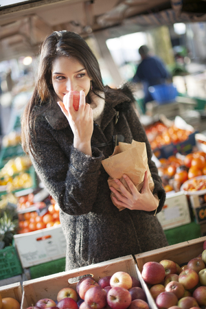 young woman buying apples on a street market Stock Photo