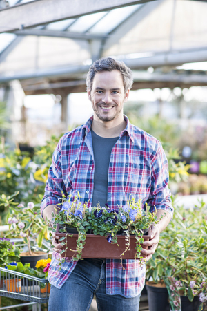 handsome man posing with a flower pot in her arms in a garden ce