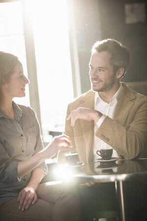 handsome couple talking and drinking coffee in a bar Stock Photo