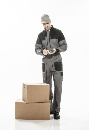 Portrait of a delivery man on isolated background using digital device