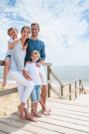 happy family standing on a wood pontoon in front of the sea in summer