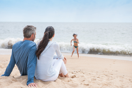A youg couple is looking at their child while she is playing in the waves