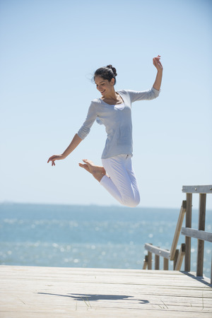young woman full of energy jumping on a pontoon in front of the sea