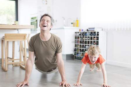 father and son  are doing pushups and having fun  at home Foto de archivo