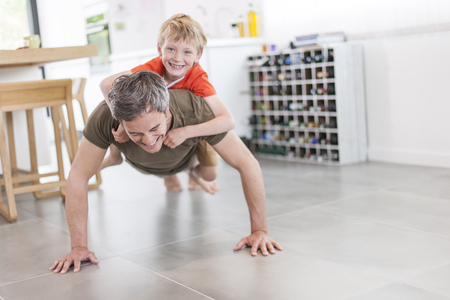father and son  are doing pushups and having fun  at home Stock Photo