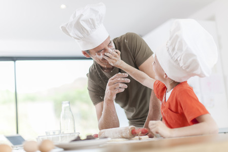 a father and his son preparing a cake in the kitchen Stock Photo