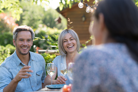 summer. Group of friends gathered around a table in the garden Stock Photo