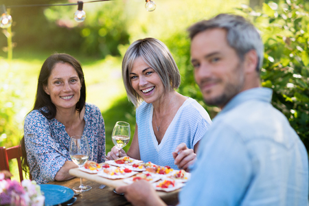 Summer, a group of friends in their forties gather at dinner in garden