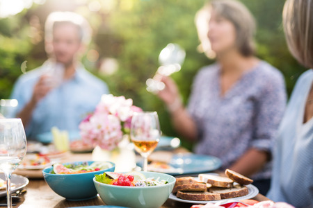 Focus on a colored salad in a bowl, Friends gather to share meal