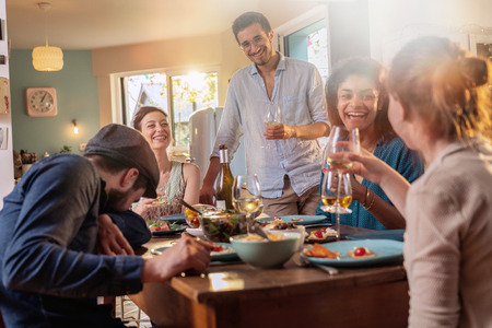Mixed group of friends having fun while sharing a meal Stock Photo