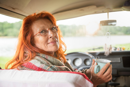 senior hipster woman in her van looking at camera