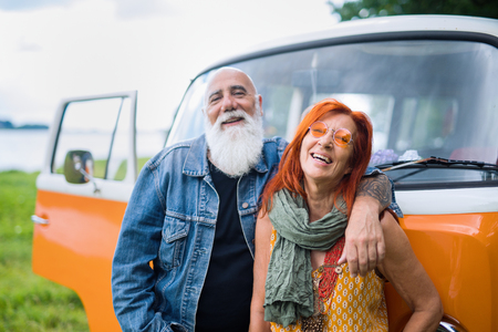 An old hipster couple posing in front of their vintage van Banque d'images
