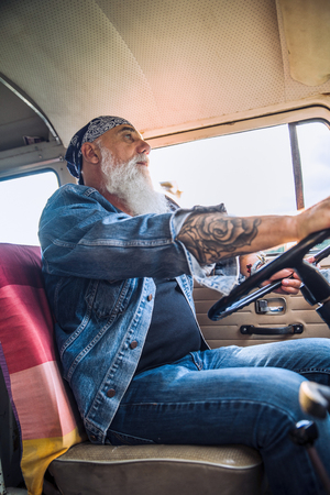 Portrait of a senior hipster driving his vintage van.