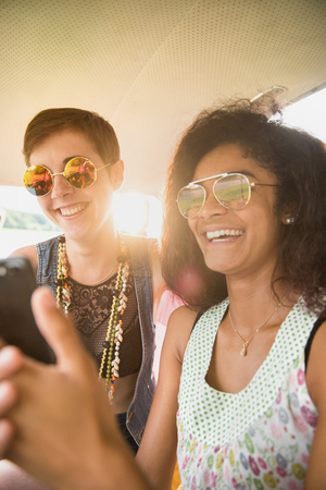 Two young mixed women having fun using a smartphone.