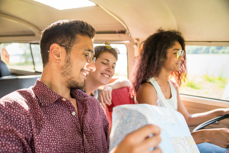 Mixed group of happy young people going on holiday in a van