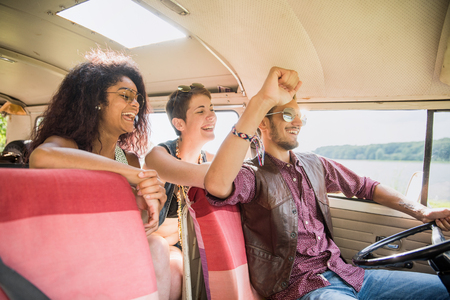 Mixed group of young people going on holiday in a vintage van Stock Photo