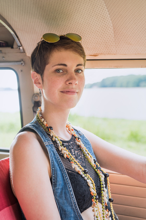 Portrait of a young hipster female goes on holiday with her van Stock Photo