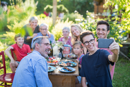 during a bbq a boy does a selfie with the whole family Stock Photo
