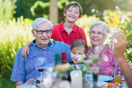 Grandparents with their grandchildren in the garden in summer Stock Photo