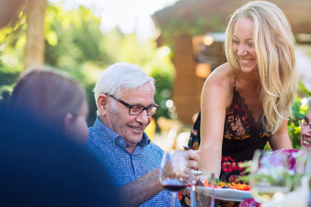 During a picnic, young woman shares a dish to her grandfather Stock Photo