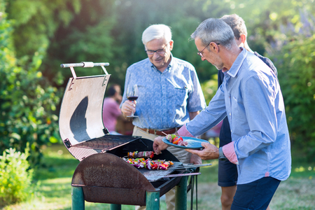 Family gathered for a bbq in the garden. men are grilling meat Stock Photo