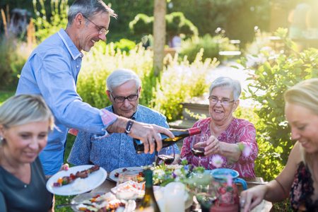 cheerful family gathered around a table for a bbq in the garden