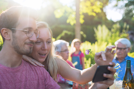 During a family bbq a young couple does a selfie on their phone Stock Photo