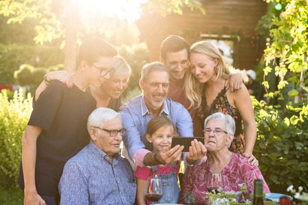 During a bbq, the family have fun sharing a video on a phone Stock Photo