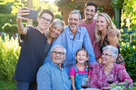 during a bbq a teenager does a selfie with the whole family