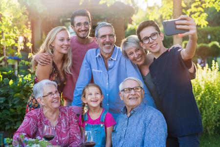 lors d'un barbecue un adolescent fait un selfie avec toute la famille